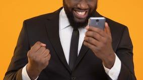 Gelukkig Afro-Amerikaans mannetje dat in smartphone van de kostuumholding ja gebaar, loterij toont stock video