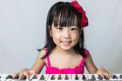 Gelukkig Aziatisch Chinees meisje dat elektrisch pianotoetsenbord speelt royalty-vrije stock fotografie