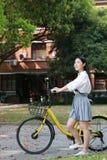 Gelukkig Aziatisch Chinees mooi meisje die een de studentenkostuum van de fietsslijtage in school berijden Stock Afbeelding