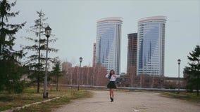 Gelukkig Aziatisch meisje die op weg in korte eenvormige school springen Modeldraaien en glimlachen stock footage