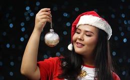 Gelukkig Aziatisch Meisje die Santa Costume Holding Christmas Bauble dragen royalty-vrije stock afbeeldingen