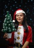 Gelukkig Aziatisch Meisje die Santa Costume Holding Small Christmas T dragen stock fotografie
