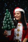 Gelukkig Aziatisch Meisje die Santa Costume Holding Small Christmas T dragen stock foto's