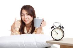 Gelukkig Aziatisch meisjeskielzog omhoog, duimen omhoog met wekker en coff Royalty-vrije Stock Foto