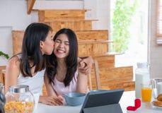 Gelukkig Aziatisch paar lesbisch krijgend huwelijk en het tonen van ring aan vriend voor tablet met videopraatje LGBTQ-levensstij stock foto's