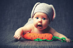 Gelukkig babykind in kostuum een konijnkonijntje met wortel op een grijs Royalty-vrije Stock Foto