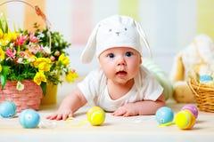 Gelukkig babykind met Paashaasoren en eieren en bloemen Stock Afbeelding