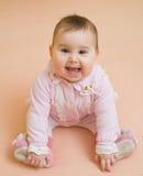 Gelukkig babymeisje dat bij het bed ligt Stock Fotografie