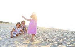 Gelukkig babymeisje en haar zusters die in zand op een mooi strand spelen royalty-vrije stock afbeelding