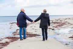 Gelukkig bejaard hoger paar die op strand lopen Stock Foto's
