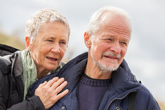 Gelukkig bejaard hoger paar die op strand lopen stock fotografie