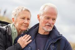 Gelukkig bejaard hoger paar die op strand lopen stock afbeeldingen