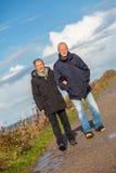 Gelukkig bejaard hoger paar die op strand lopen stock afbeelding