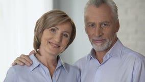 Gelukkig bejaard paar die elkaar bekijken en bij camera, reclame glimlachen stock footage