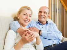 Gelukkig bejaard paar samen op bank in huis Stock Afbeeldingen
