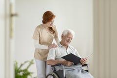 Gelukkig bejaarde in de rolstoel die een boek lezen tijdens bezoek stock foto's