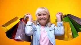 Gelukkig bejaarde die vele het winkelen zakken tonen, vrije tijd, zakgeld royalty-vrije stock afbeeldingen