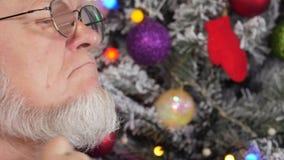 Gelukkig bejaarde die zijn grijze baard met kam op achtergrond van Kerstboom in slingers, groene UFOballen, proton purper stuk sp stock videobeelden