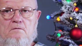 Gelukkig bejaarde die zijn grijze baard met kam op achtergrond van Kerstboom in slingers, groene UFOballen, proton purper stuk sp stock footage