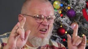 Gelukkig bejaarde die zijn grijze baard met kam op achtergrond van Kerstboom in slingers, groene UFOballen, proton purper stuk sp stock video