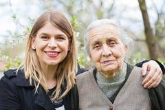 Gelukkig bejaarde met werker uit de hulpverlening openlucht - de lente royalty-vrije stock fotografie