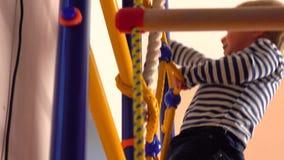 Gelukkig beklimt weinig blonde jongen op de ladder in speelkamer Van de van het jong geitjesport, succes of voltooiing concepten  stock footage