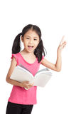 Gelukkig bestudeerde weinig Aziatisch meisje een boek en een punt Stock Foto's