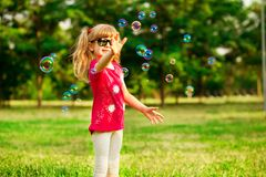 Gelukkig blaast weinig blond meisje zeepbels in de zomerpark royalty-vrije stock afbeelding
