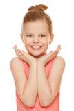 Gelukkig blij meisje die die met handen dichtbij gezicht glimlachen, op witte achtergrond wordt geïsoleerd Stock Afbeelding