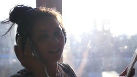 Gelukkig blij meisje met hoofdtelefoons op hoofd en met telefoon in handen die zich voor venster in zonlicht bevinden Slowmotion stock video
