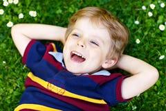 Gelukkig bloeit weinig blond kind die met blauwe ogen op het gras met madeliefjes leggen in het park Op warme de zomerdag kid stock afbeelding