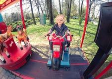 Gelukkig blond babymeisje in een carrousel in Chindia-Park Targoviste Roemenië Royalty-vrije Stock Afbeeldingen