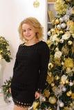 Gelukkig blond meisje die wijd en tegen Kerstmis glimlachen stellen tre Royalty-vrije Stock Foto