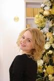 Gelukkig blond meisje die wijd en tegen Kerstmis glimlachen stellen tre Royalty-vrije Stock Fotografie
