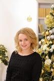 Gelukkig blond meisje die wijd en tegen Kerstmis glimlachen stellen tre Stock Foto's