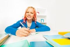 Gelukkig blond meisje met color hair do homework Royalty-vrije Stock Afbeeldingen