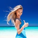 Gelukkig blond meisje op strand, die okeyteken tonen. stock fotografie