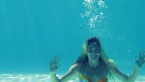 Gelukkig blonde die in zwembad en het golven springen stock video