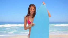 Gelukkig brunette die een blauwe surfplank houden stock videobeelden
