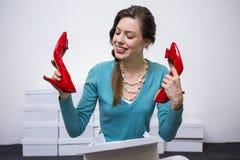 Gelukkig brunette die rode schoenen steunen royalty-vrije stock foto