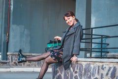 Gelukkig brunette in kleding en laag het winkelen Toont nieuwe schoenen Royalty-vrije Stock Foto