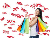 Gelukkig brunette met de kleurrijke zakken Korting en verkoopsymbolen: 10% 20% 30% 50% 70% Royalty-vrije Stock Foto's