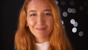 Gelukkig close-up die Kaukasische gembermeisje het kijken camera glimlachen cheerfully en het lopen van vage zwarte achtergrond,  stock videobeelden