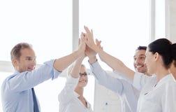 Gelukkig commercieel team die hoogte vijf in bureau geven Stock Afbeeldingen