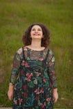 Gelukkig curvy meisje met krullend haar in het landschap stock foto
