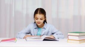 Gelukkig de lezingsboek of handboek van het schoolmeisje thuis stock footage