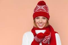 Gelukkig de wintermeisje in gebreide warme hoed en vuisthandschoenen die een kop in handen houden De geïsoleerde vrouw van Smilli Royalty-vrije Stock Foto's