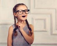 Gelukkig denkend jong geitjemeisje in manierglazen met opgewekte emotiona stock foto's