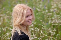Gelukkig die blondemeisje door bloemen wordt omringd Royalty-vrije Stock Afbeelding