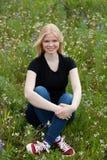 Gelukkig die blondemeisje door bloemen wordt omringd Royalty-vrije Stock Fotografie